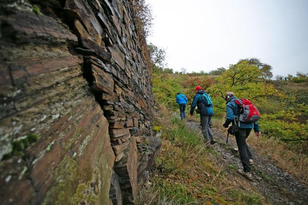 Wanderer gehen an einer Schiefermauer auf schmalem Pfad einen Berg hoch.